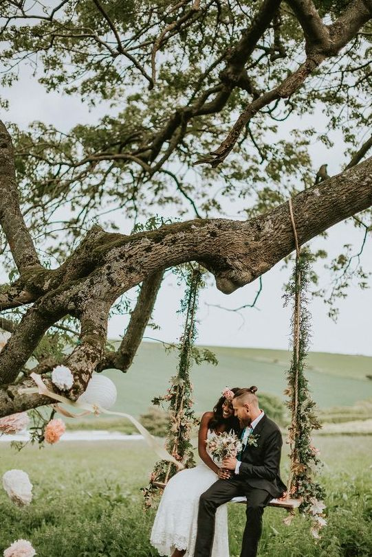 a swing decorated with textural greenery and some wildflowers
