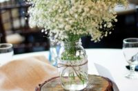 12 a wood slice with a jar wapped with lace and twine and baby's breath