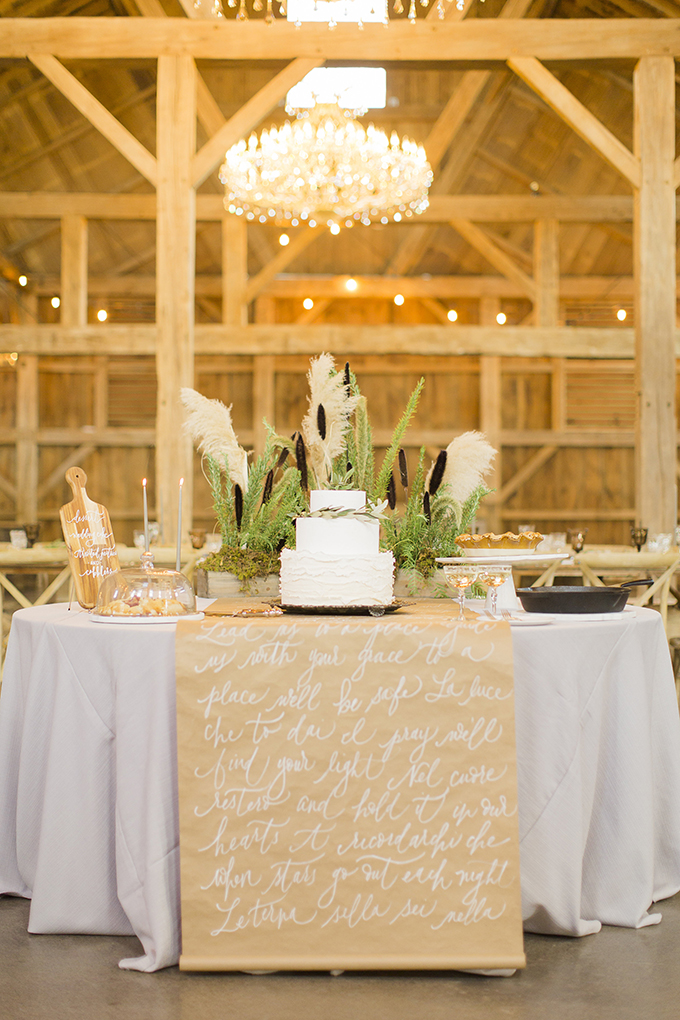 The cake table decorated with a paper runner and some greenery