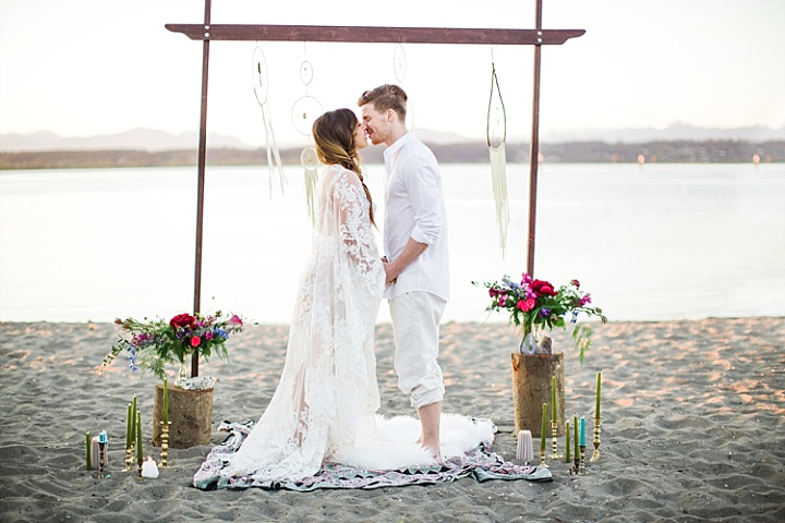 The wedding arch was placed on the beach, it was decorated with fringe, flowers and candles
