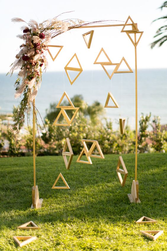 an arch with wooden triangles hanging and bold flowers on the corner