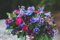 14 a lush floral centerpiece with violet, fuchsia and burgundy flowers ina  gold vase