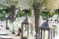 14 hurricane lamps and tall vases of baby's breath