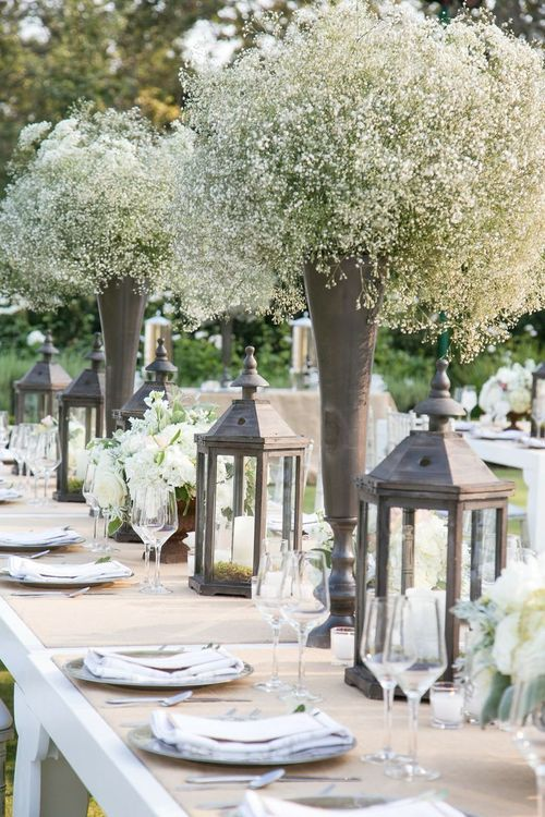 hurricane lamps and tall vases of baby's breath