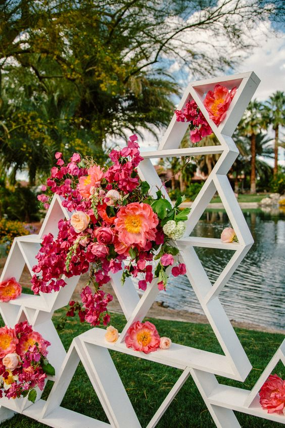 white triangle wedding backdrop with lush bold pink and fuchsia flowers