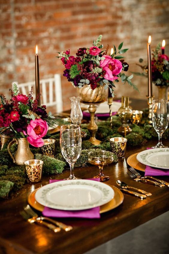 burgundy and hot pink centerpieces in gold vases create lush decor