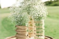 15 glass vases wrapped with twine and burlap and baby's breath