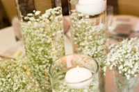 16 baby's breath placed inside tall galss vases and floating candles on top