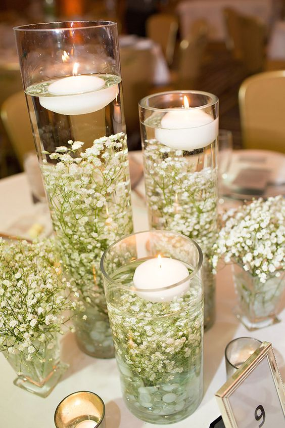 baby's breath placed inside tall galss vases and floating candles on top