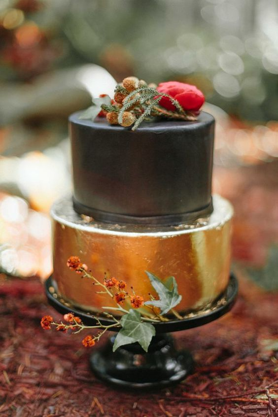 gold leaf and black wedding cake with herbs and wildflowers
