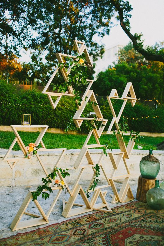 triangle installation with greenery and some blooms