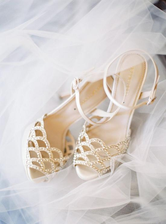 white peep toe and laser cut wedding heels with a fish scale pattern and rhinestones
