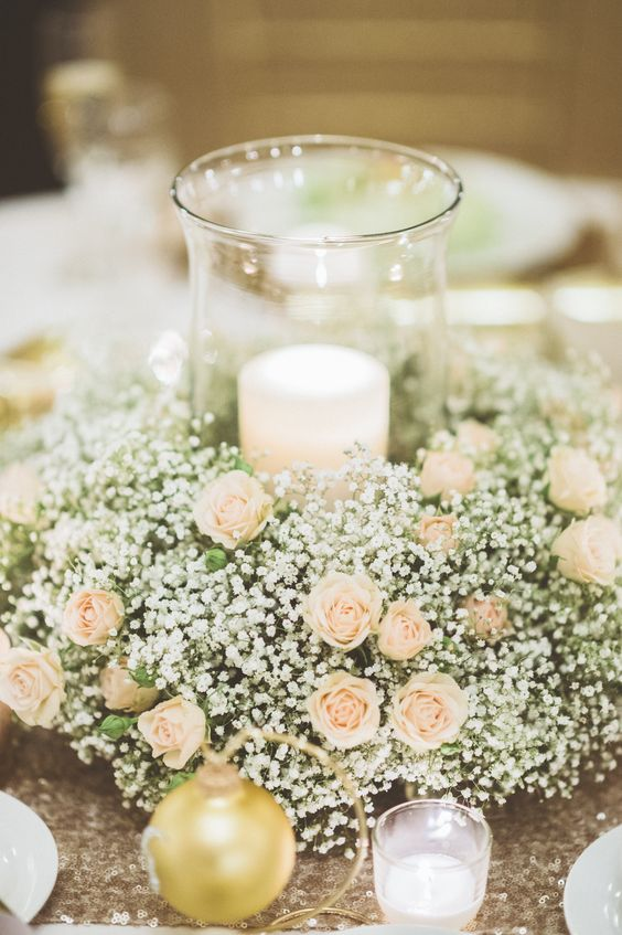 a baby's breath and blush roses wreath with a large glass candle holder