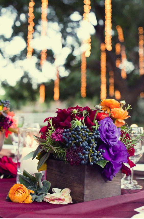 lovely low box centerpiece with burgundy, violet and orange blooms and blue berries
