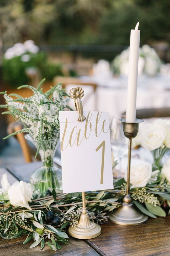 olive branches with olives and greenery in vases
