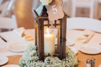 20 a baby's breath wreath with a candle lantern topepd with a white rose