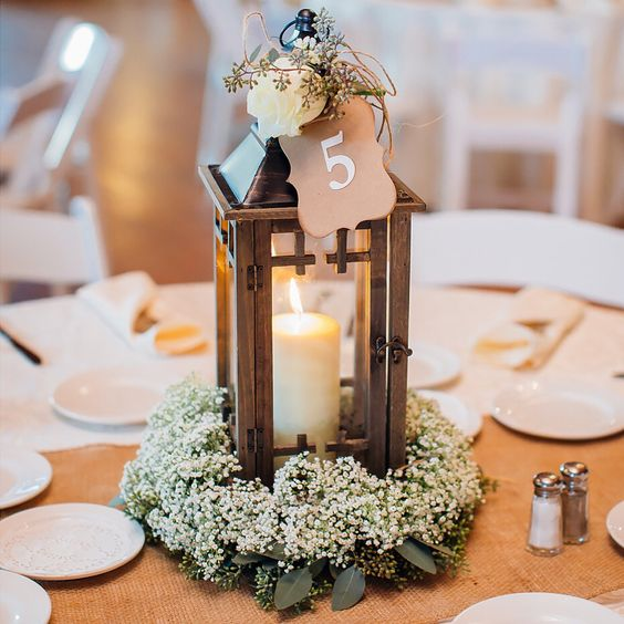 a baby's breath wreath with a candle lantern topepd with a white rose