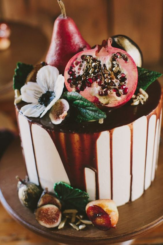 a decadent fig and pomegranate topped fall wedding cake with chocolate dripping