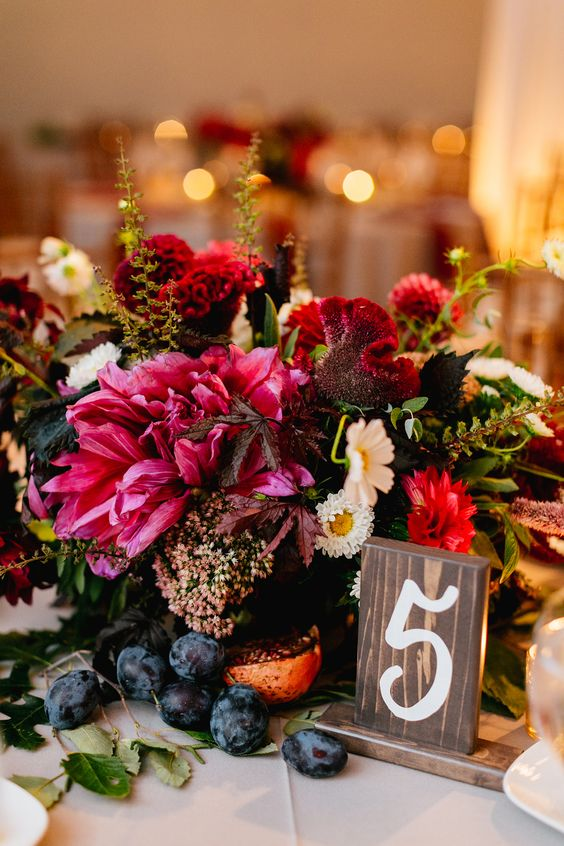 dark pink and bold red lush floral centerpiece with grapes wows