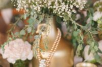 22 a gold spray paint bottle with baby's breath and strands of pearls