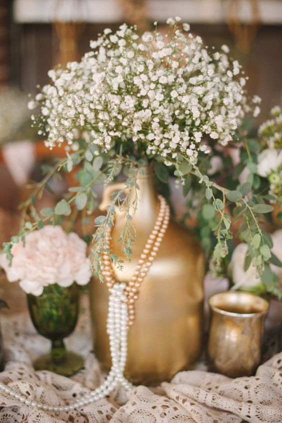 a gold spray paint bottle with baby's breath and strands of pearls