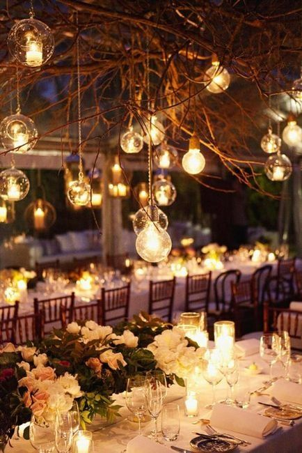 candle lanterns and large bulbs hanging from the branches create a mood