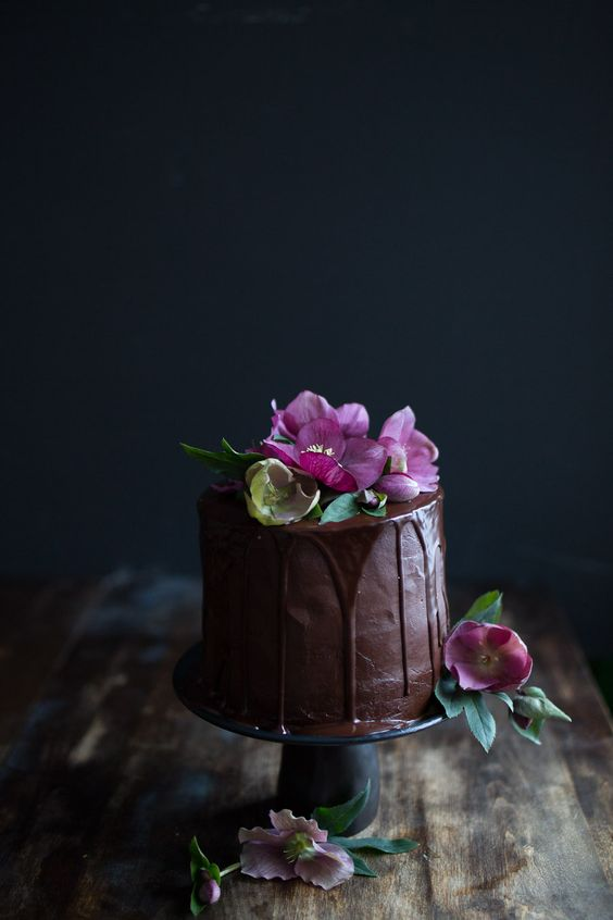 chocolate wedding cake with chocolate dripping and bold purple blooms
