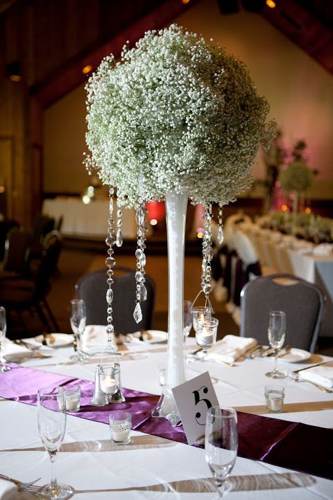 a large baby's breath ball on a glass stand with hanging crystals