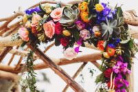 23 a wedding arch decorated with orange, violet and fuchsia flowers and greenery