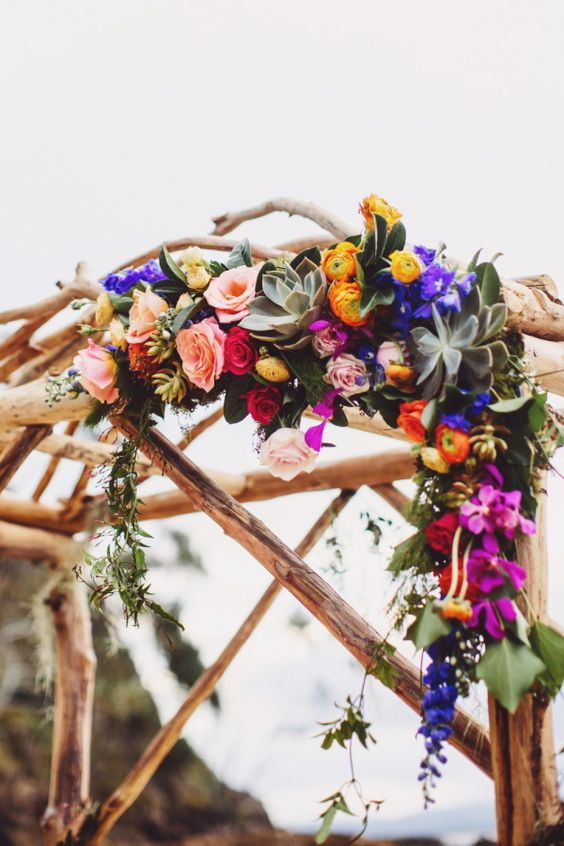 a wedding arch decorated with orange, violet and fuchsia flowers and greenery