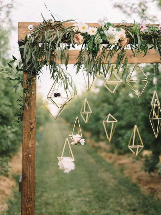 a wooden arch covered in delicate florals & hanging geometric figures