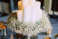24 a metallic bowl with baby's breath and lots of pillar candles