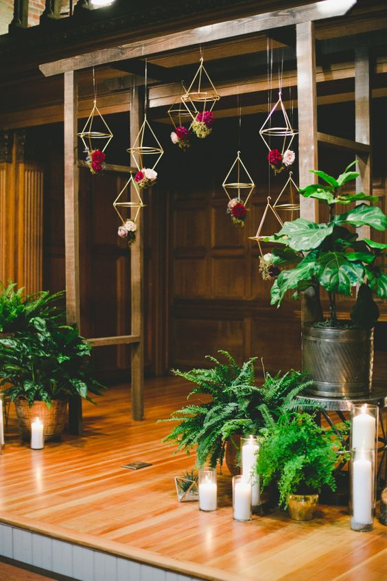 an indoor wooden arch with hanging geometric decor and bold flowers