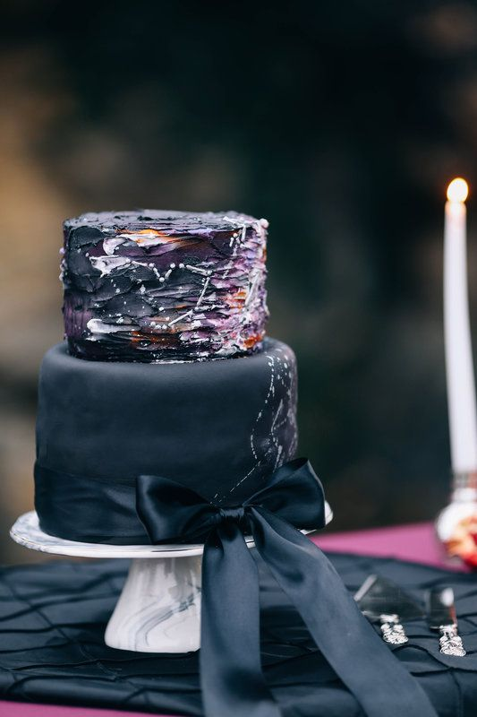 black and purple iced ccake with constellation decor and a black ribbon bow