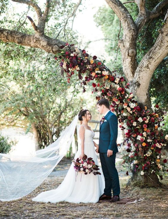 burgundy, red and orange flower tree decor to use as a wedding backdrop