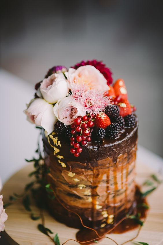 chocolate wedding cake with metallic decor, fresh berries and blush blooms
