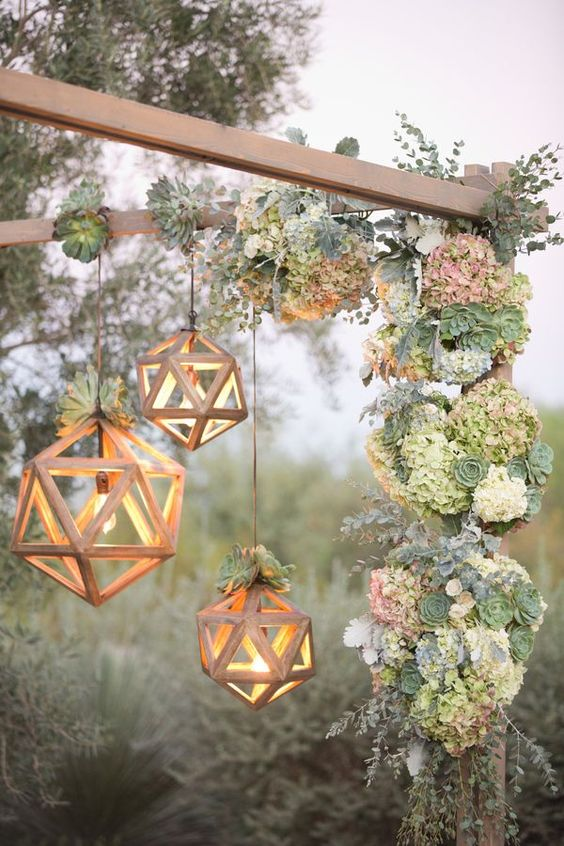 dimensional geometric lights with bulbs inside and topped with succulents