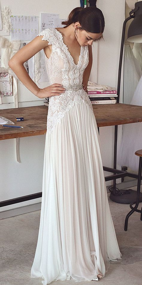 modern romantic wedding dress with a V neck, a pleated skirt and a lace bodice