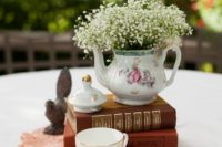 25 a stack of books, a tea cup and a teapot with baby's breath and a doily