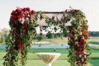 25 floral draped ceremony arbor with greenery, red, burgundy and pink blooms