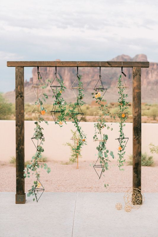 geometric desert wedding arbor with hanging greenery and color-coordinated flowers scattered throughout