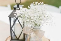 26 a wood slice with a candle lantern and a jar with baby's breath