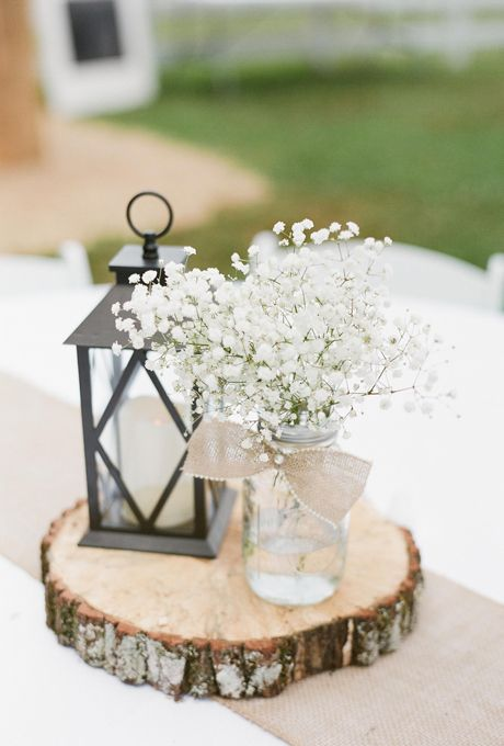 a wood slice with a candle lantern and a jar with baby's breath
