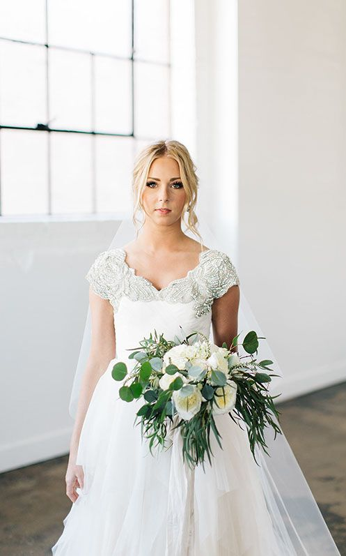 a ballgown with a V neckline and gold beading on it and cap sleeves
