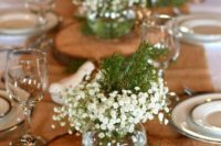 27 a wood slice with greenery, baby's breath and evergreens in a glass vase
