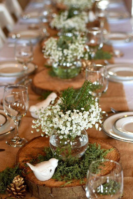 a wood slice with greenery, baby's breath and evergreens in a glass vase