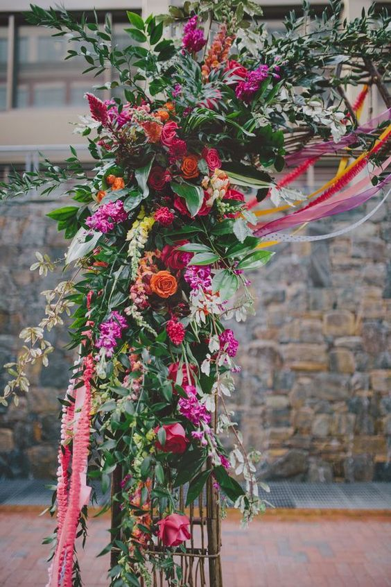 hot pink, red and orange flower arch decor with lush greenery
