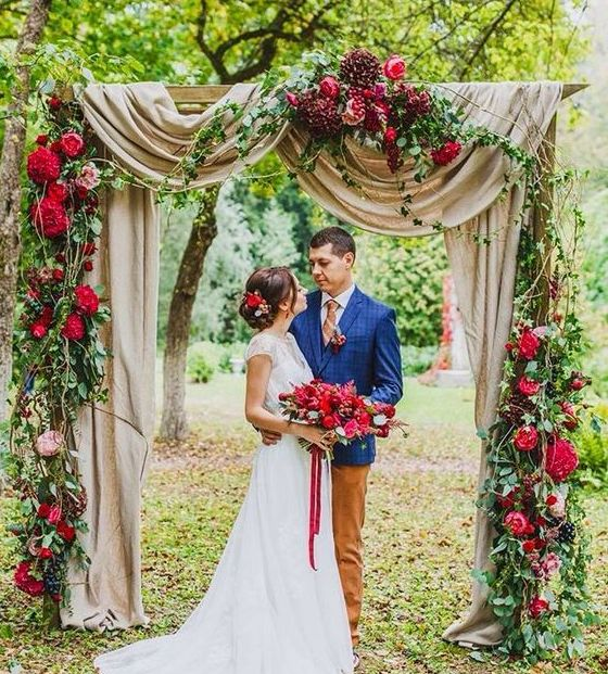 hot red and burgundy flowers on the arch with flowy fabric