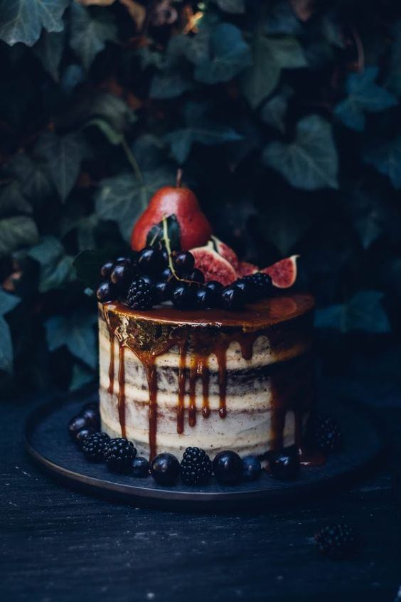 layered dripping semi naked wedding cake with pears, figs, blackberries and grapes