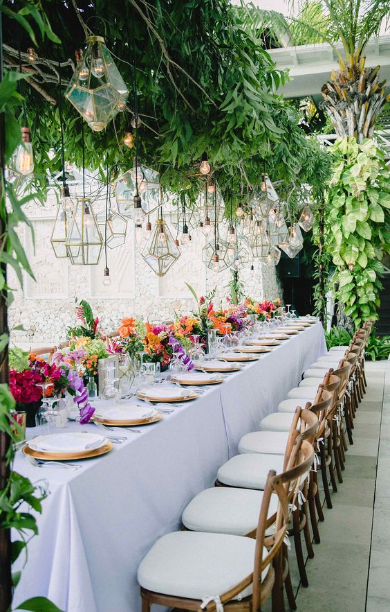 lush greenery decor over the table with geometric lanterns